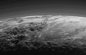 Vista en blanco y negro de Norgay Montes (en primer plano a la izquierda), Hillary Montes (horizonte a la izquierda), y Sputnik Planitia (derecha) Vista cercana a la puesta del sol que incluye varias capas de neblina atmosférica.